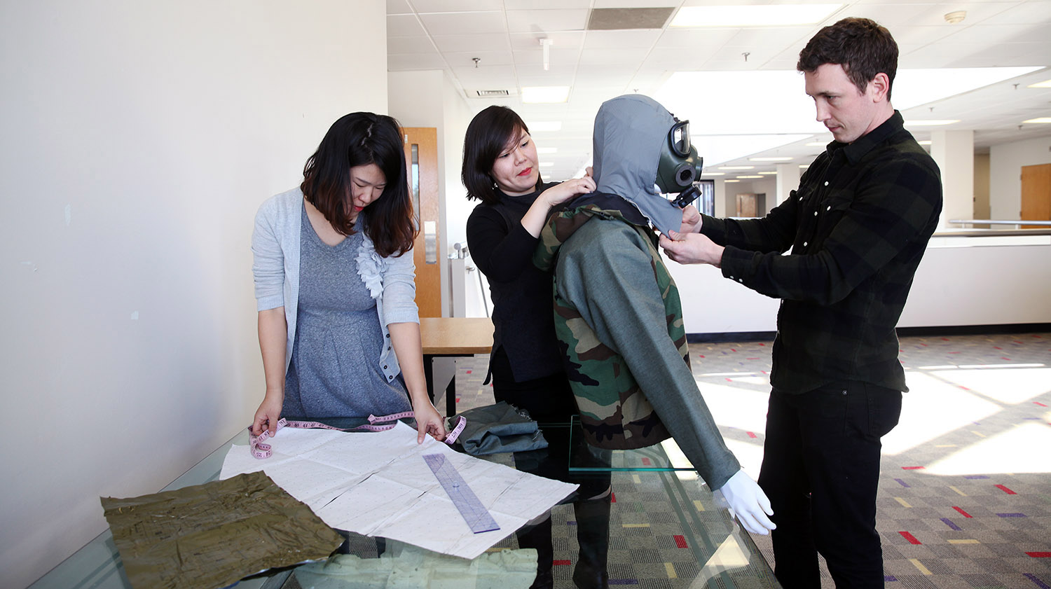 a group of three team members work on a prototype for a defense department competition
