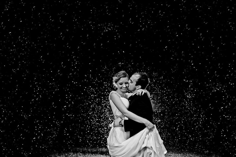 Bride and groom stand in the rain