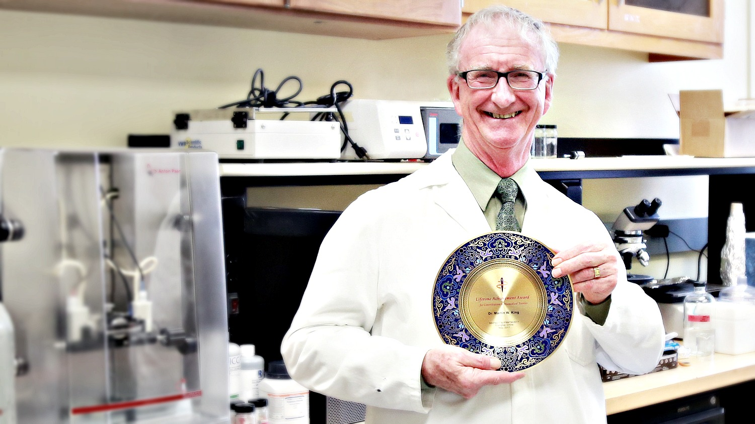 Dr. Martin King of NC State's College of Textiles wears a lab coat and holds his lifetime achievement award