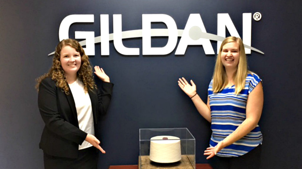 NC State Wilson College of Textiles student Mollie Fisher and fellow intern Maggie stand in front of Gildan logo