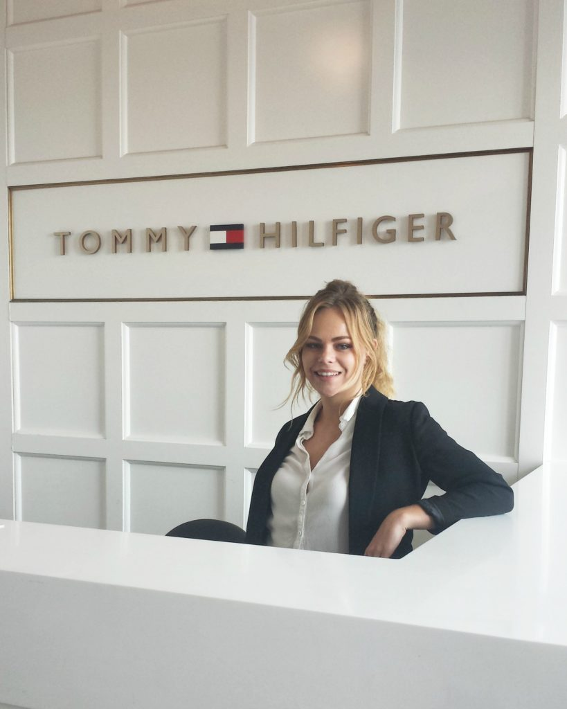 NC State Wilson College of Textiles student Olivia Weikmann behind desk at Tommy Hilfiger