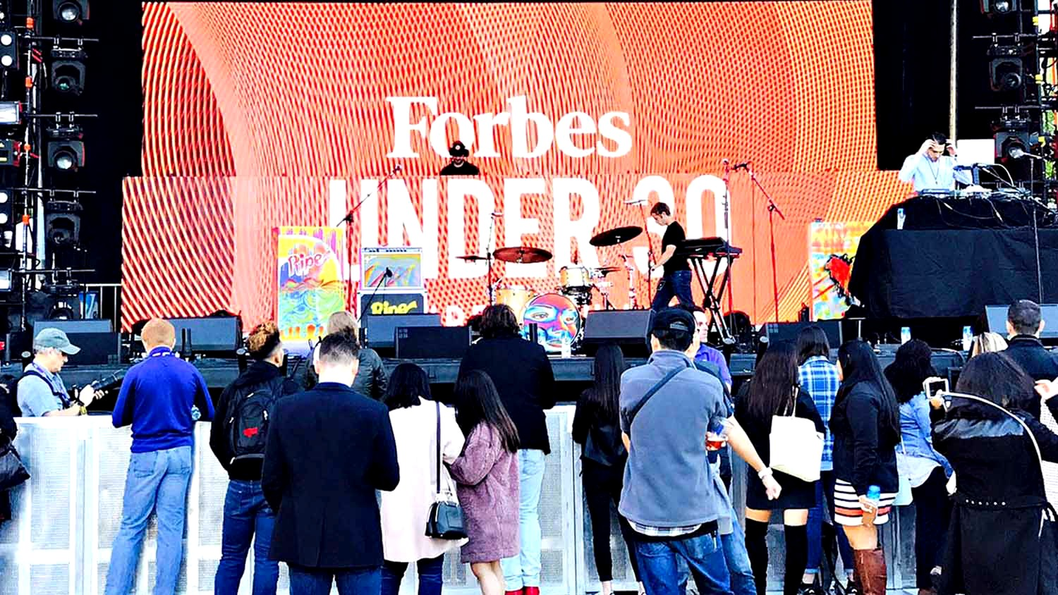 "Musician performs in front of orange backdrop inscribed with ""Forbes Under 30"""