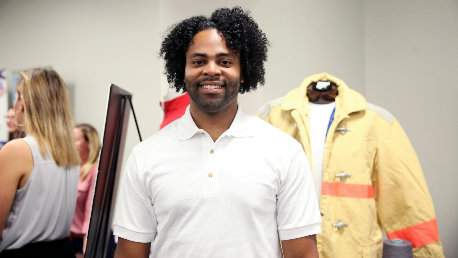 Elton Lawrence stands in front of Pharr Yarns booth at the College of Textiles career fair