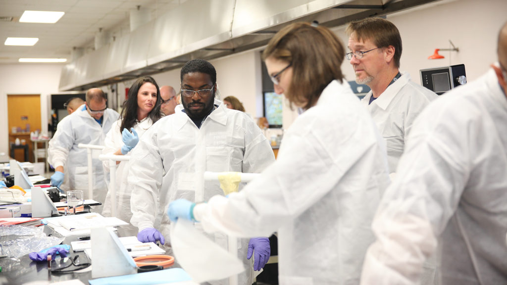 Attendees of Bloodstain Pattern Analysis on Textiles workshop experiment in the lab, led by NC State Wilson College of Textiles professor Dr. Stephen Michielsen