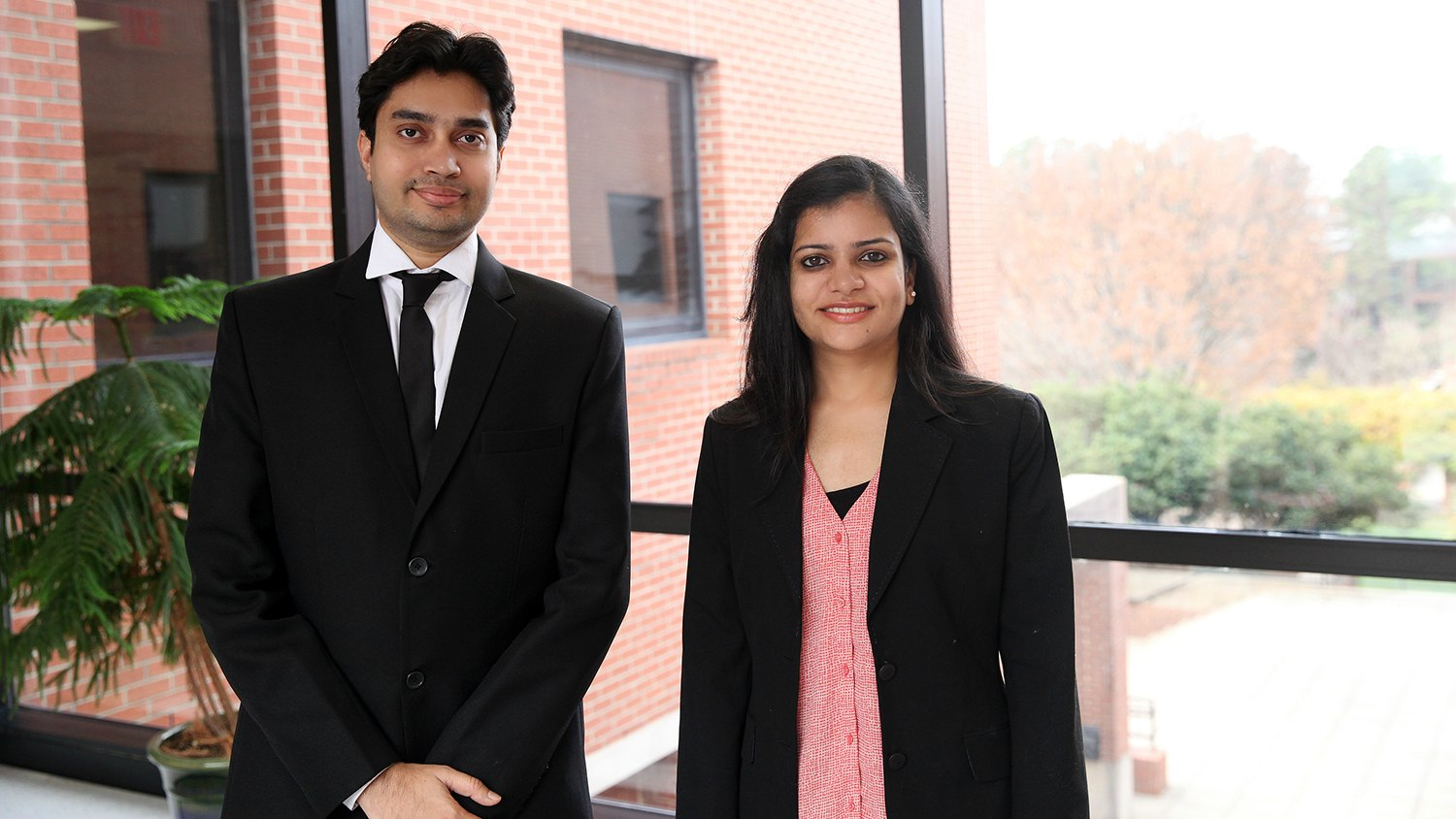Tushar Bambharoliya and Radhika Vaid stand in front of window at NC State's College of Textiles