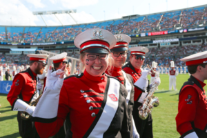 "Amanda Gregory, in her NC State marching band uniform, puts up a ""wolfie."""