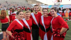 5 NC State color guard members in bright red and white uniforms face the camera