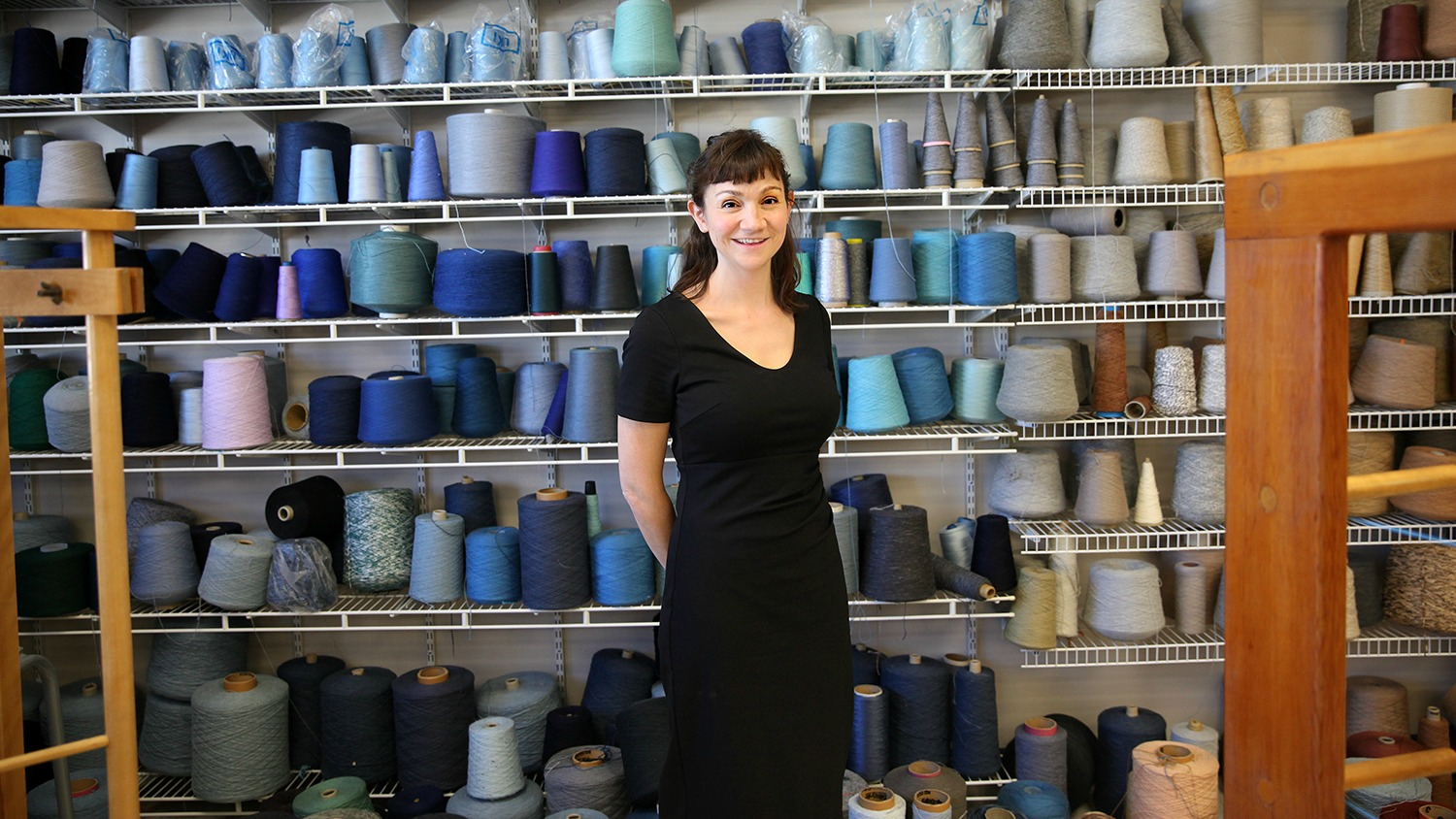 NC State TATM assistant professor Janie Woodbridge stands in front of rows of yarn in ombre hues of blue and gray