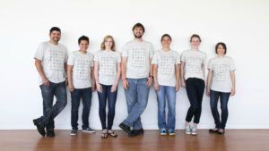 Group of 7 people in a line, wearing khaki 30 Elements t-shirts