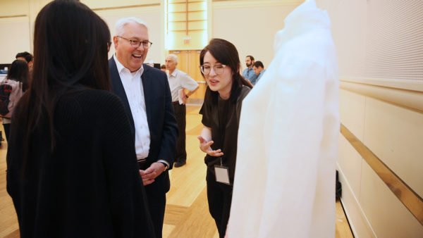 Ashley Maurice and Ngoc Nguyen show protective garments to NC State Chancellor Randy Woodson