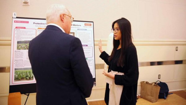 Ngoc Nguyen discusses research poster with NC State Chancellor Randy Woodson