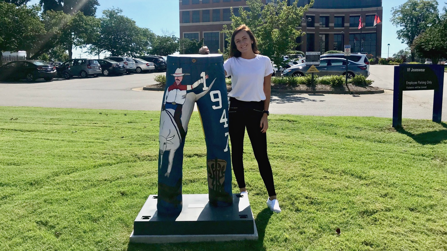 College of Textiles FTM major Anna Owen poses with a statue of a pair of jeans at Wrangler headquarters
