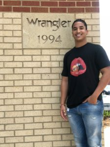 Wilson College of Textiles student Tshepo Dithane in front of Wrangler sign
