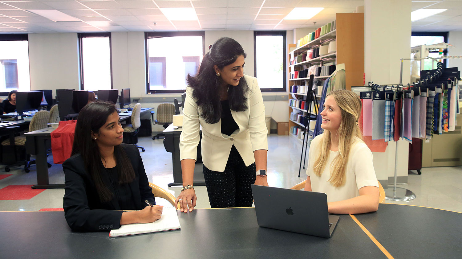 TATM professor Dr. Kavita Mathur speaks with two students