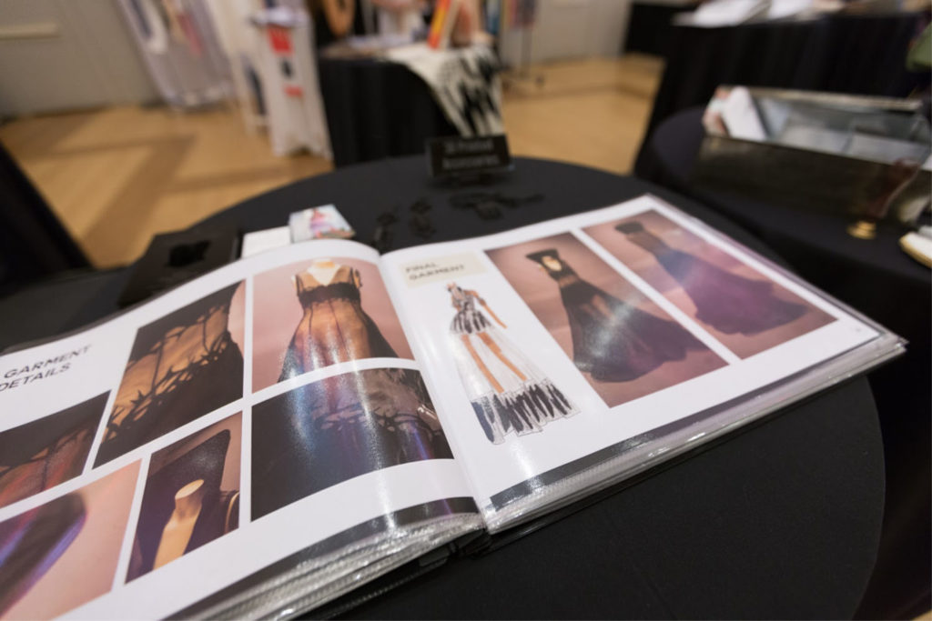 open book displaying photos and sketches of fashion designs and finished garments