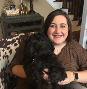 Wilson College of Textiles FTD alumna Jenna DeCandio, seated and holding little dog