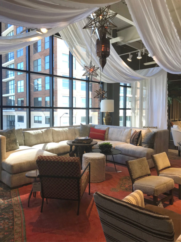 Reds and earth tones, star lanterns and ceilings draped with white fabric at Lee Industries showspace at Fall 2018 High Point Market