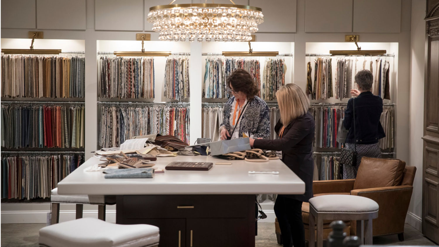 Two women look through upholstery samples at Wesley Hall at the 2018 High Point Market