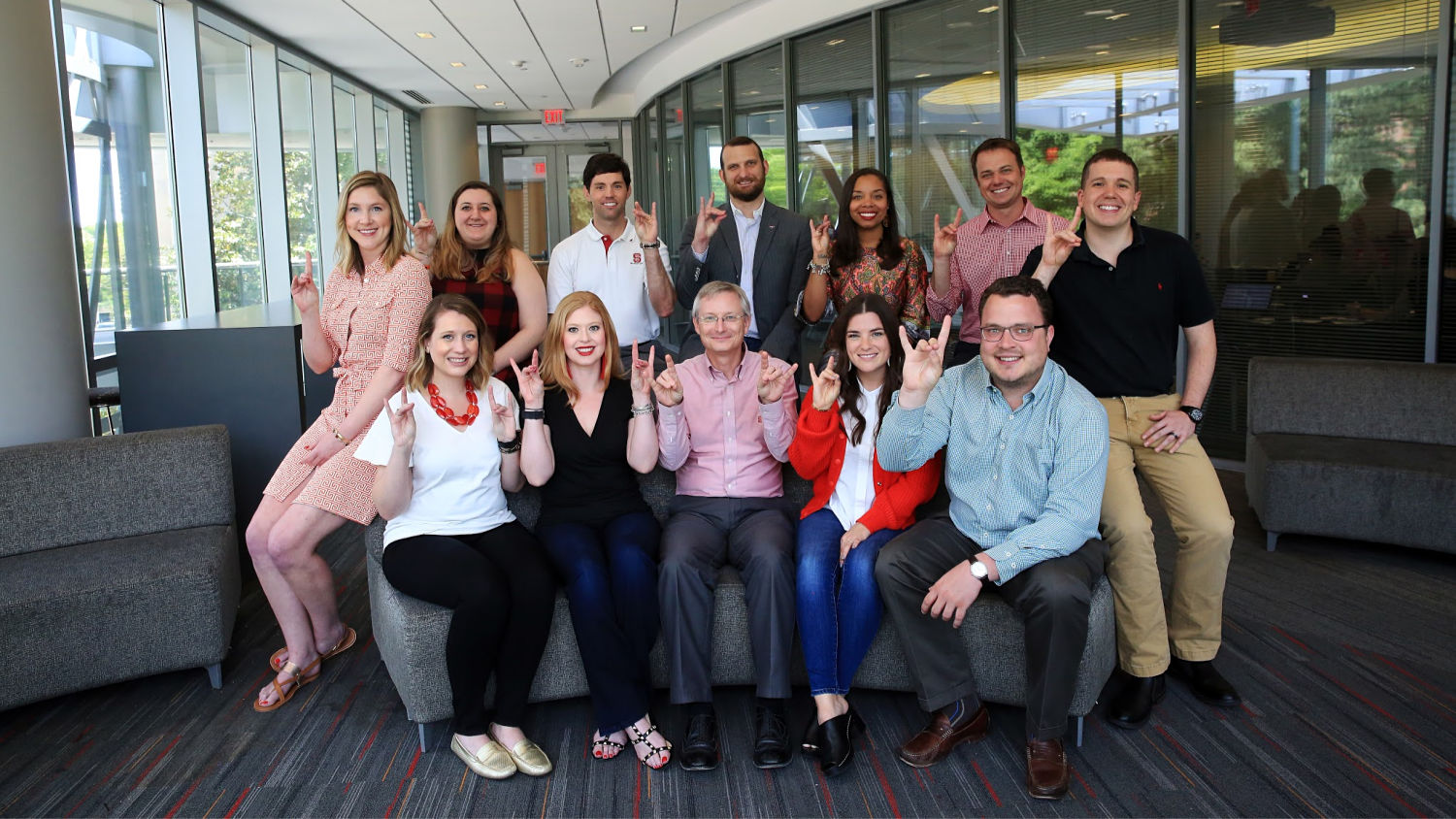 A group of Wilson College of Textiles alumni comprise the Dean's Young Alumni Leadership Council, pictured here both seated and standing, making the Wolfpack symbol