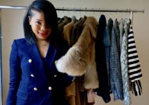 Wilson College of Textiles alumna Germanee Gerald in blue blazer in front of clothes rack