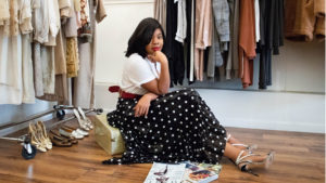 Wilson College of Textiles alumna Germanee Gerald poses in white t-shirt and polka dot maxi skirt