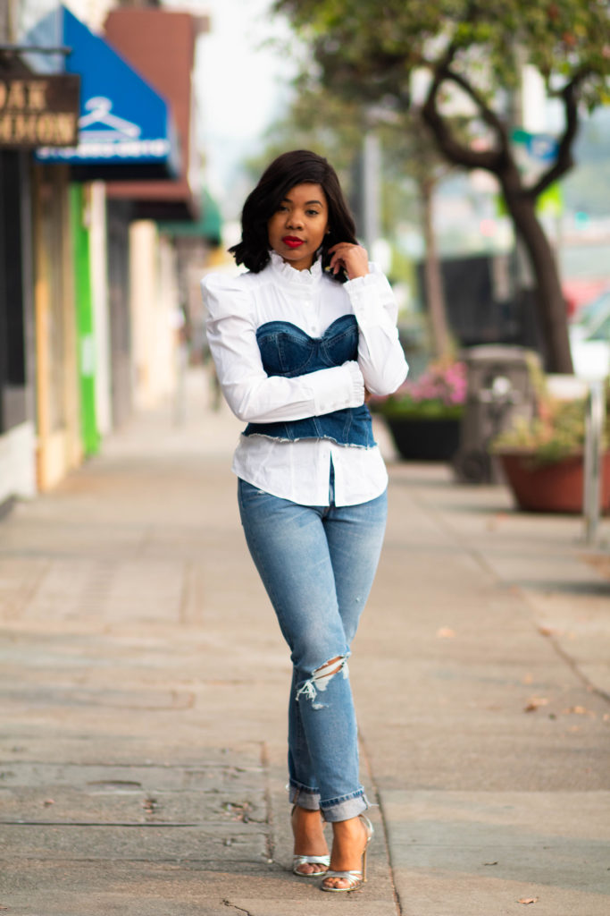 Wilson College of Textiles alumna Germanee Gerald poses in jeans and a denim bustier top over white blouse
