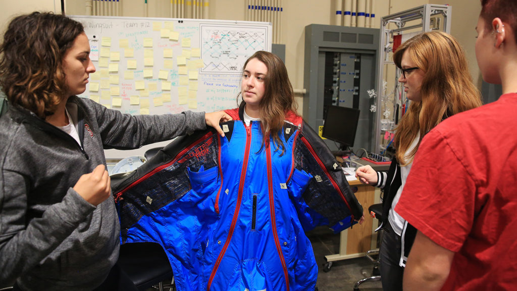 Senior design student from the Wilson College of Textiles tries on blue winged parachute suit
