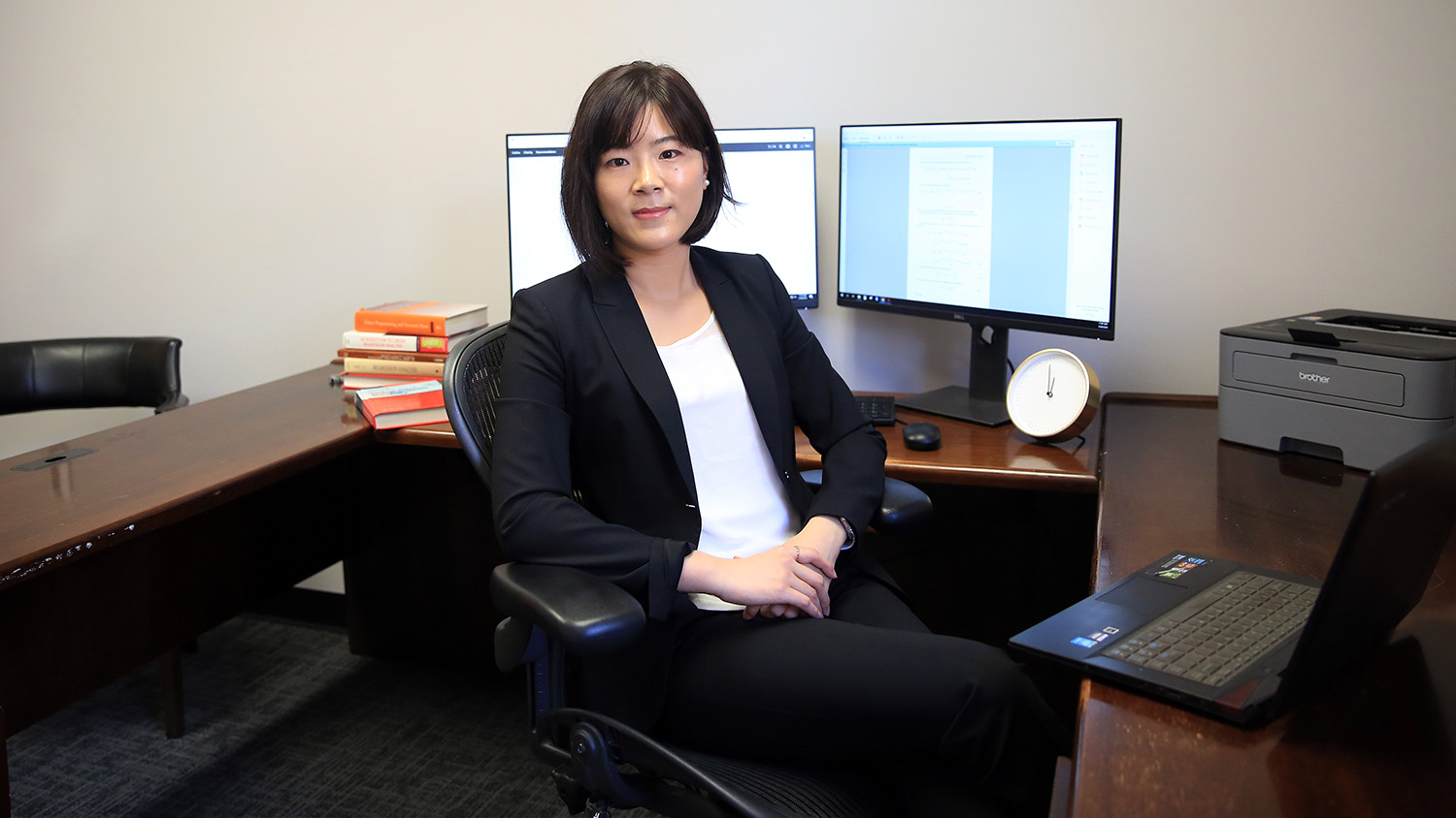 Dr. Mengmeng sitting in her office facing the camera