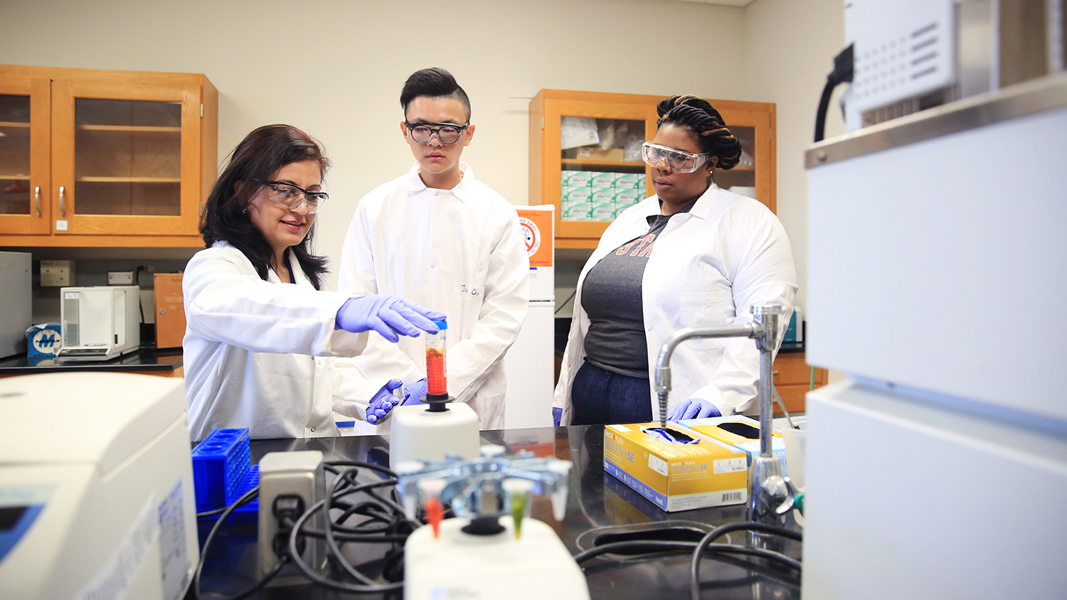 Standing in a laboratory, Dr. Budhathoki-Uprety demonstrates a testing process to two students.