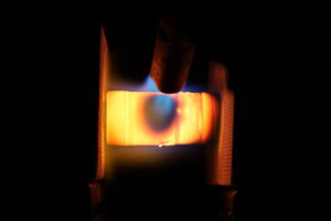 This photo was taken in complete darkness shows the superb heat resistance and thermal stability of carbon nanotube (CNT) / silicon carbide (SiC) nano hybrid structure (glowing) at 1980 °C, exposure to a propane torch burning. Research on producing ultrahigh temperature stable materials for aerospace applications