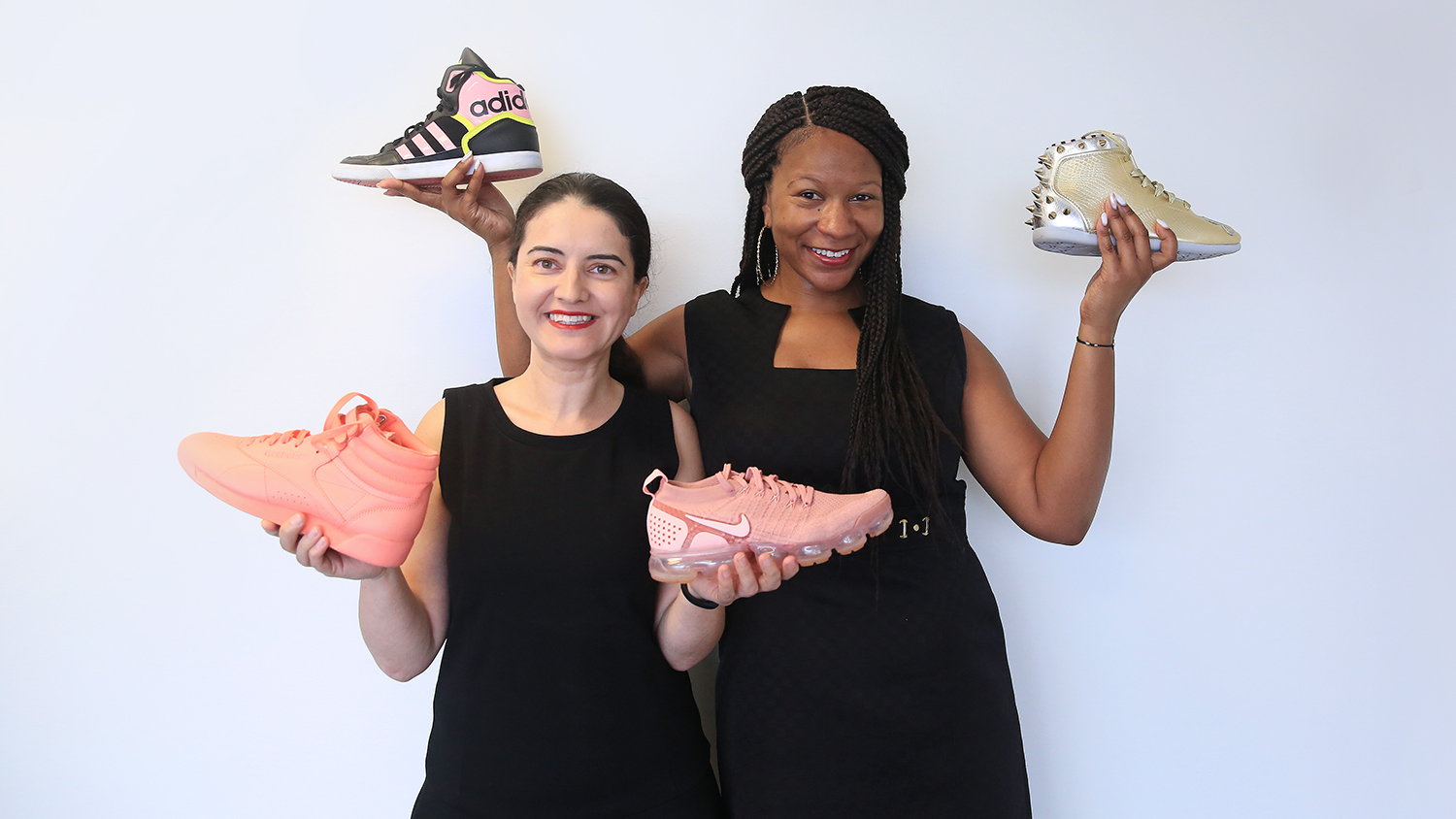 TATM assistant professor Delisia Matthews and Ph.D. student Nimet Degirmencioglu holding 4 different sneakers