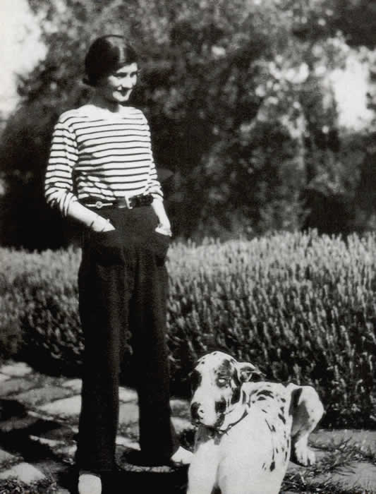 Black and white photo of a young Gabrielle Chanel outside with dog, wearing one of her signature looks of striped shirt and trousers