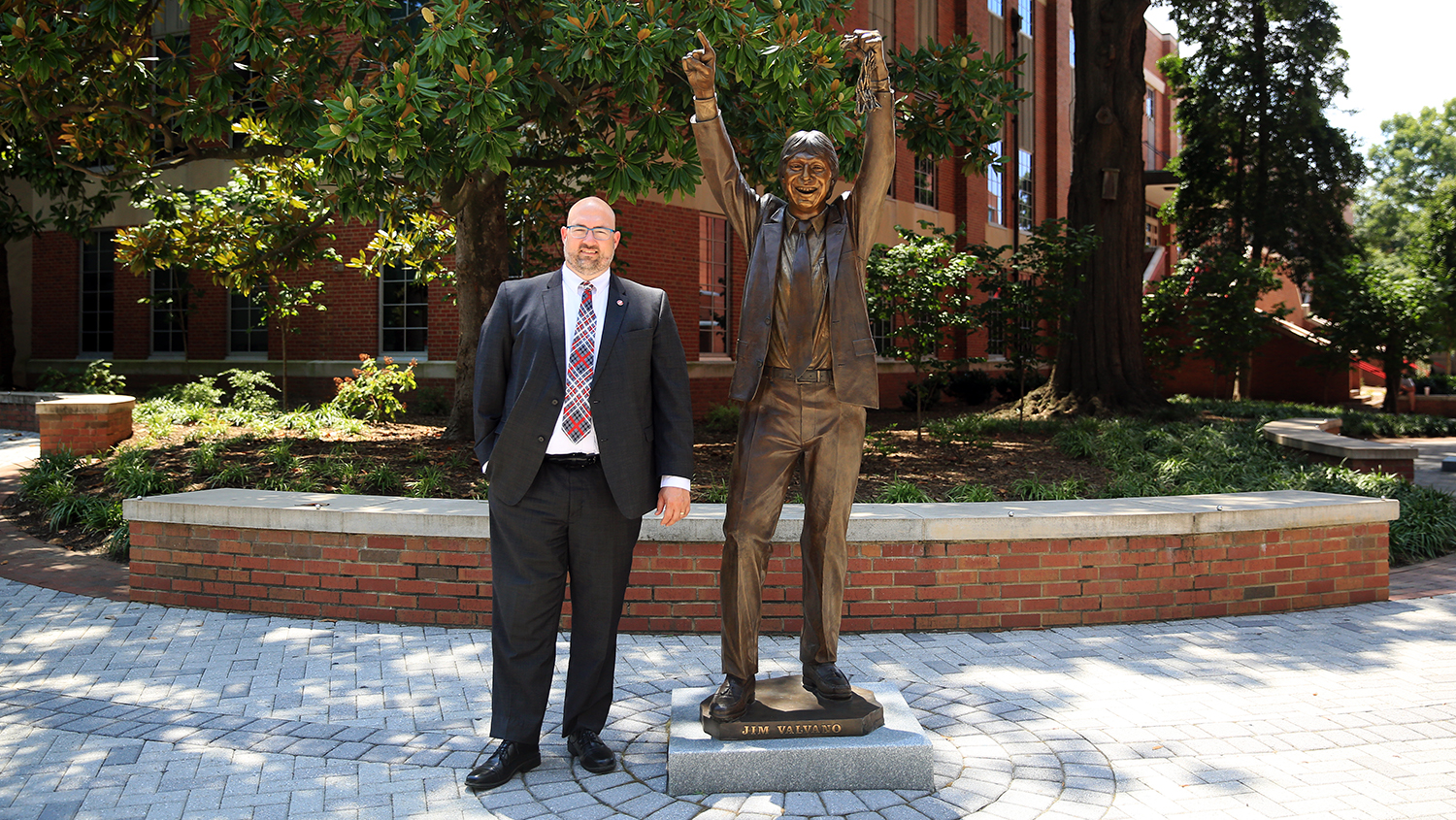 NCTF executive director Michael Ward stand next to bronze statue of Jim Valvano outside