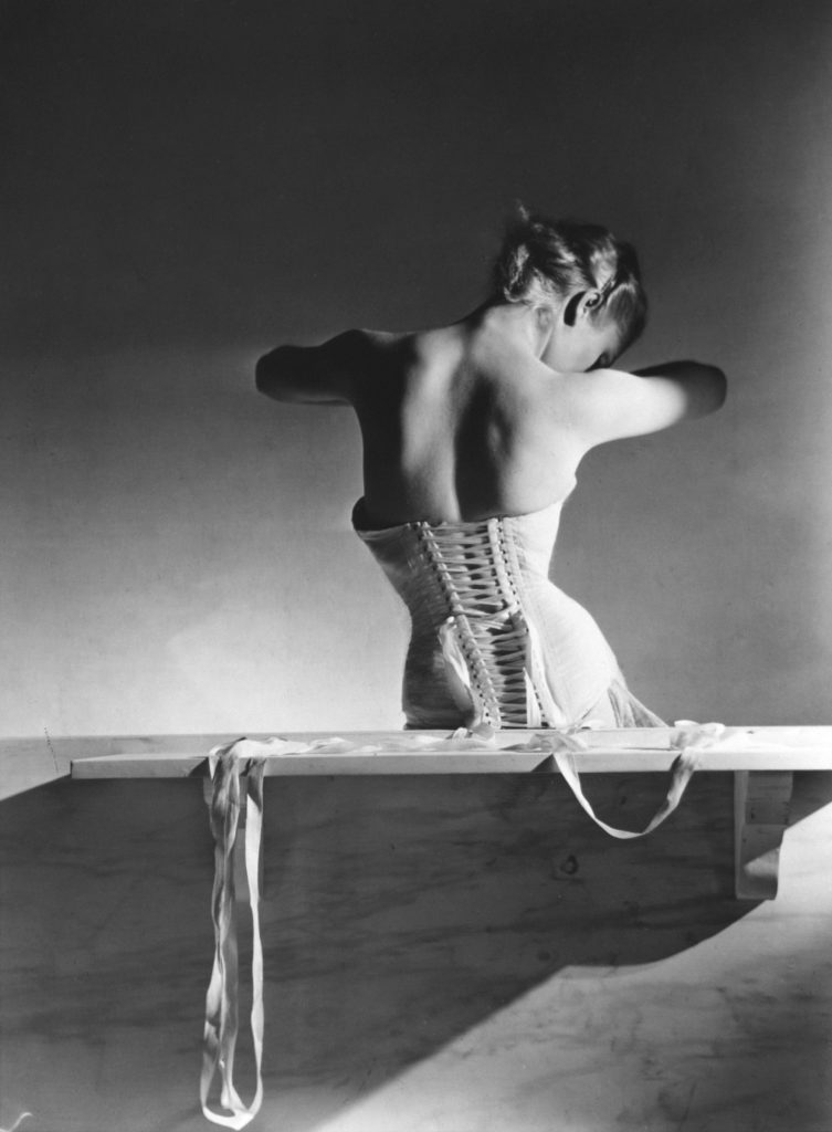 Black and white portrait of a woman wearing a corset, shot from behind. Her face is obscured. By Horst P. Horst for September 1939 issue of Vogue.