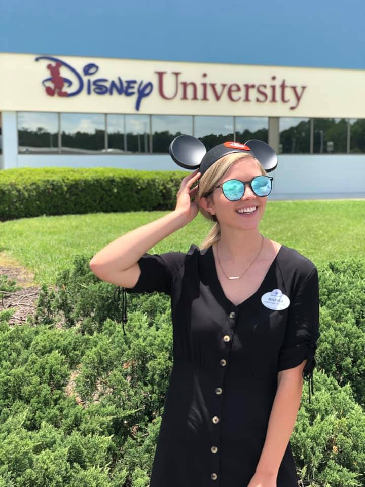 Wilson College of Textiles alumna Marisa Pridgen in mouse ears in front of Disney University building