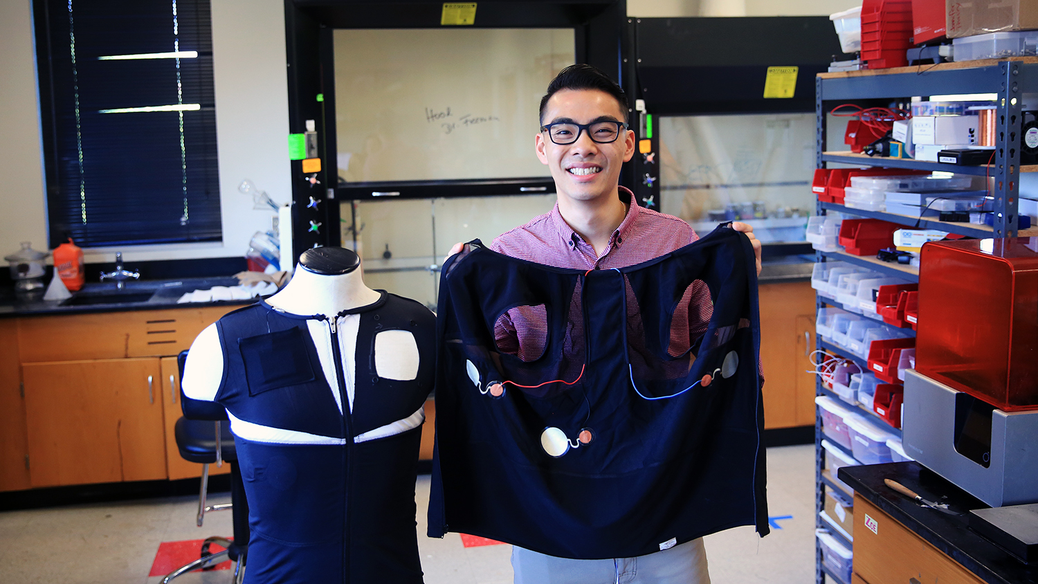 Braden Li shows off a self-powered ECG-sensing shirt