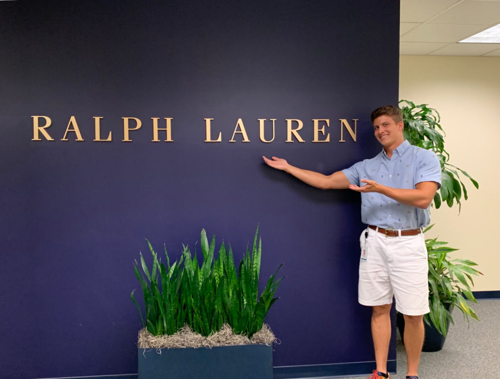 Jonathan Bethel gestures at Ralph Lauren sign on the wall beside him