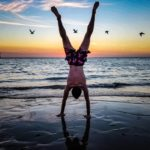 Man doing handstand on Australian beach at sunset with birds in the background