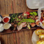 Colorful Australian charcuterie board laden with asparagus, mushroom, meats and cheeses