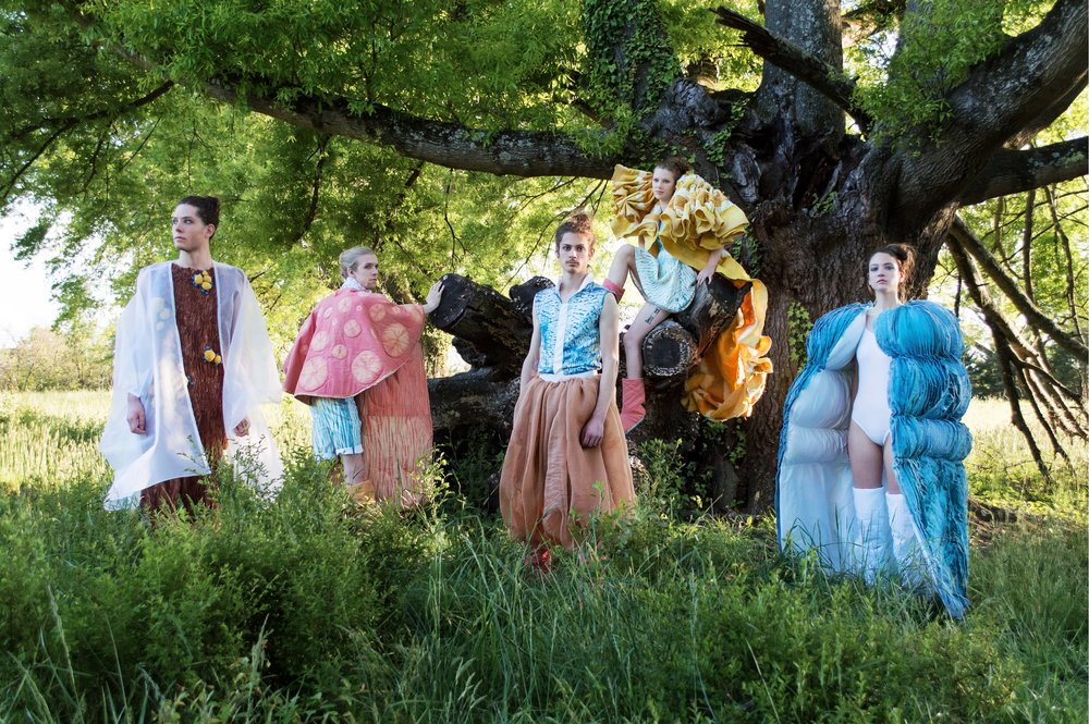Male and female models stand under a tree in a grassy field, wearing Bailey Knight's Art2Wear collection, MycoLogic, which is inspired by NC mushrooms