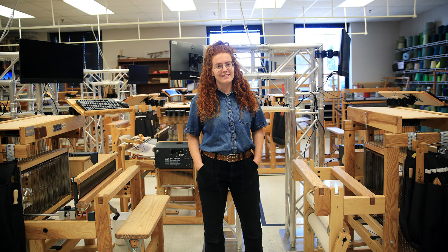 TATM studio and lab technician Bailey Knight stands with hands in pockets in weaving lab, wearing a denim shirt and black pants.