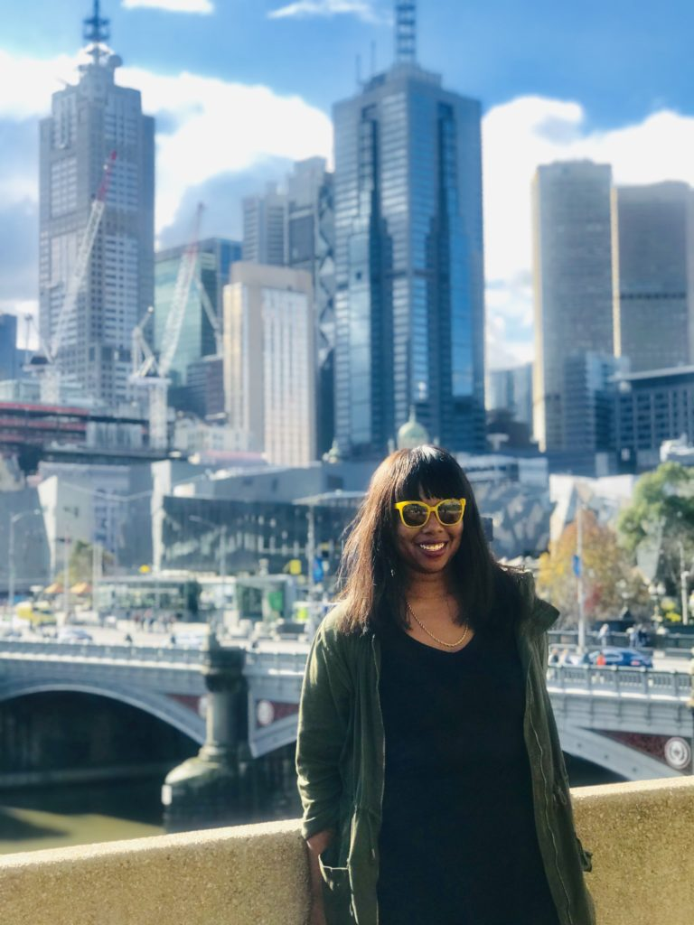 Bri Hart, in jacket and yellow-rimmed sunglasses, stands in front of skyline of Australian city.