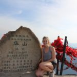 Livi Prestifilippo kneels next to plaque atop the south peak of Huashan (Mount Hua)