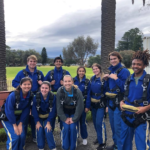 Group of study abroad students in Australia wearing blue jumpsuits as they prepare to board skydiving plane