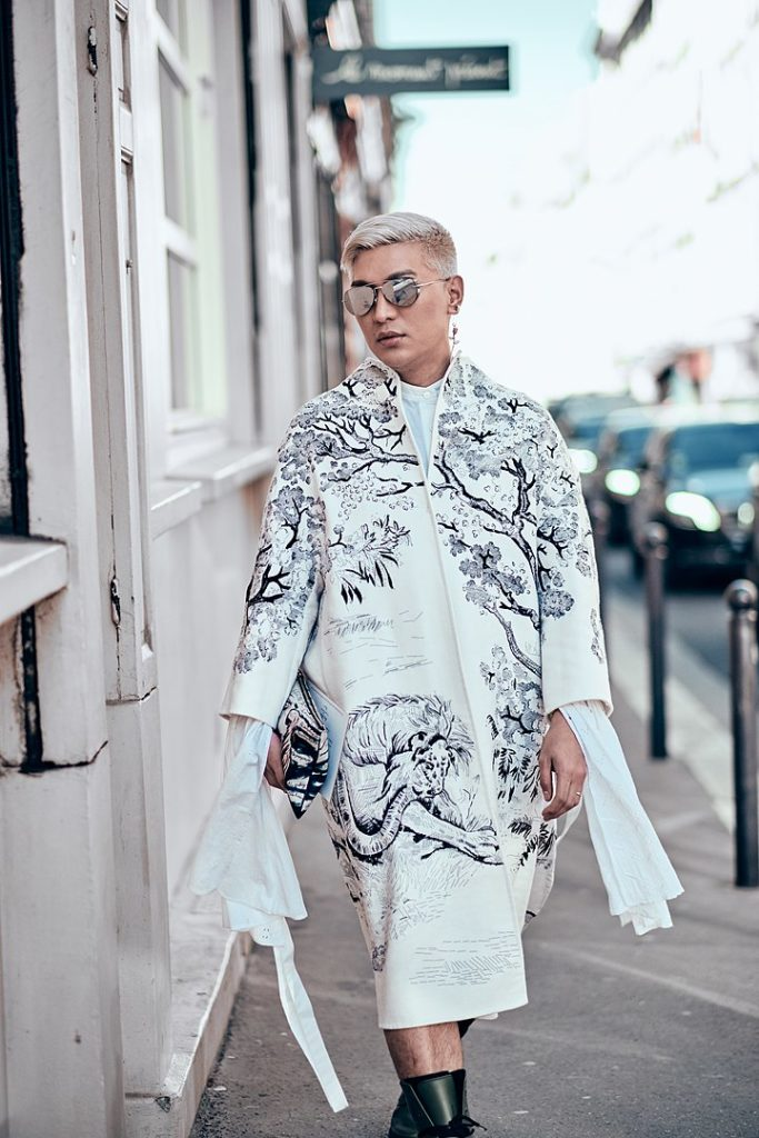 BryanBoy at Paris Fashion Week 2019 wearing long ivory coat with tree print and mirrored sunglasses