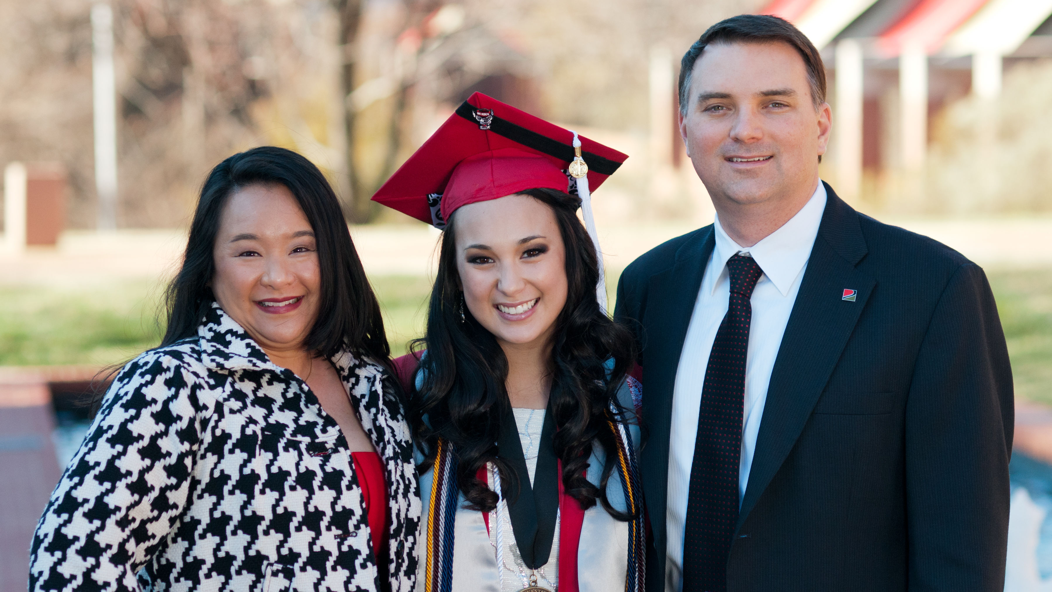 Smiling Cassia Lewis in red cap and gown flanked by her parents