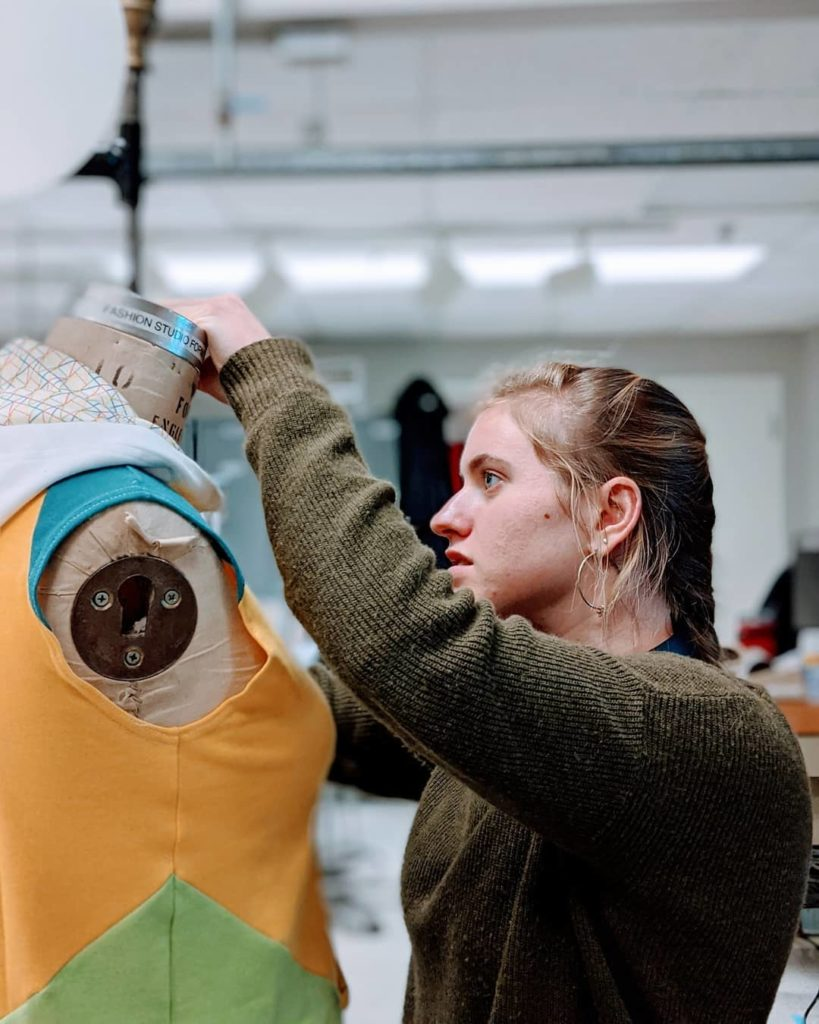 Anna Henry works on a design on a mannequin