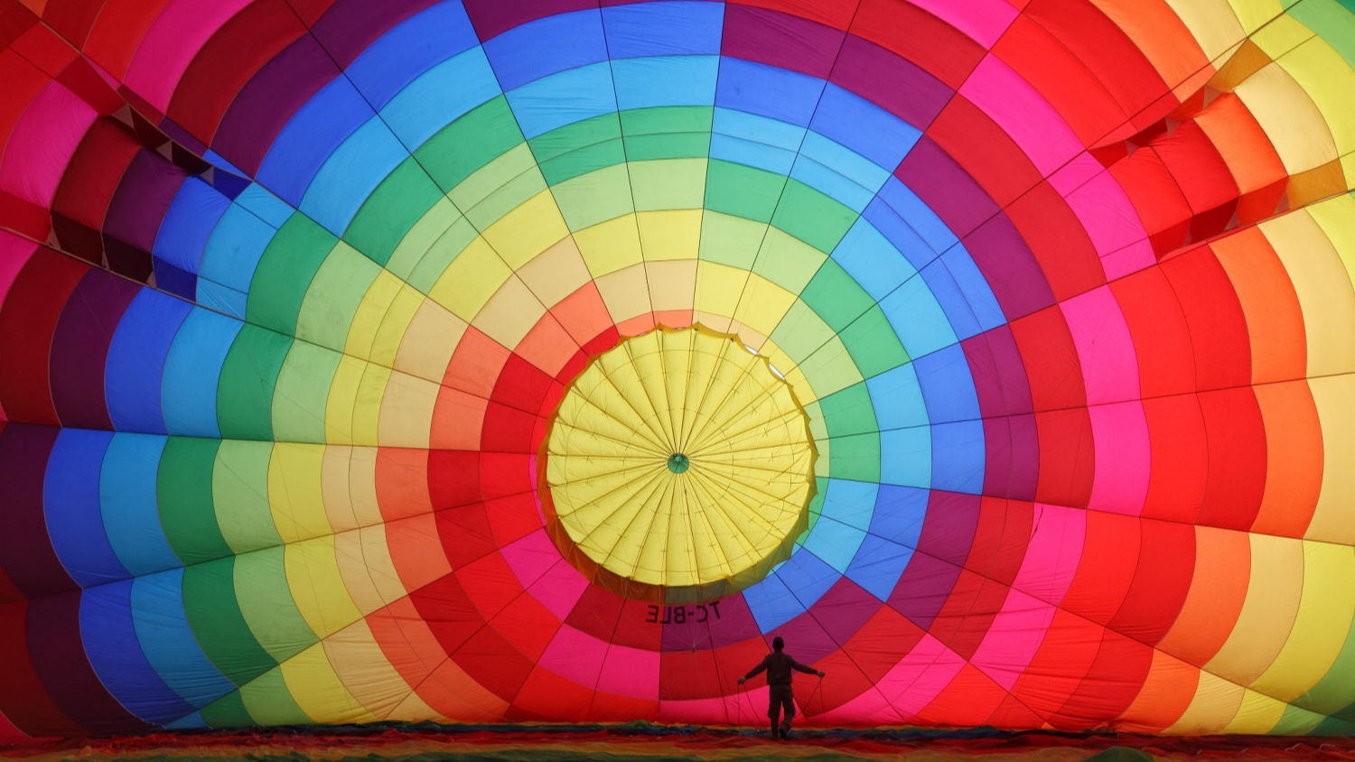 Photograph of multicolored balloon inflating, with silhouette of person
