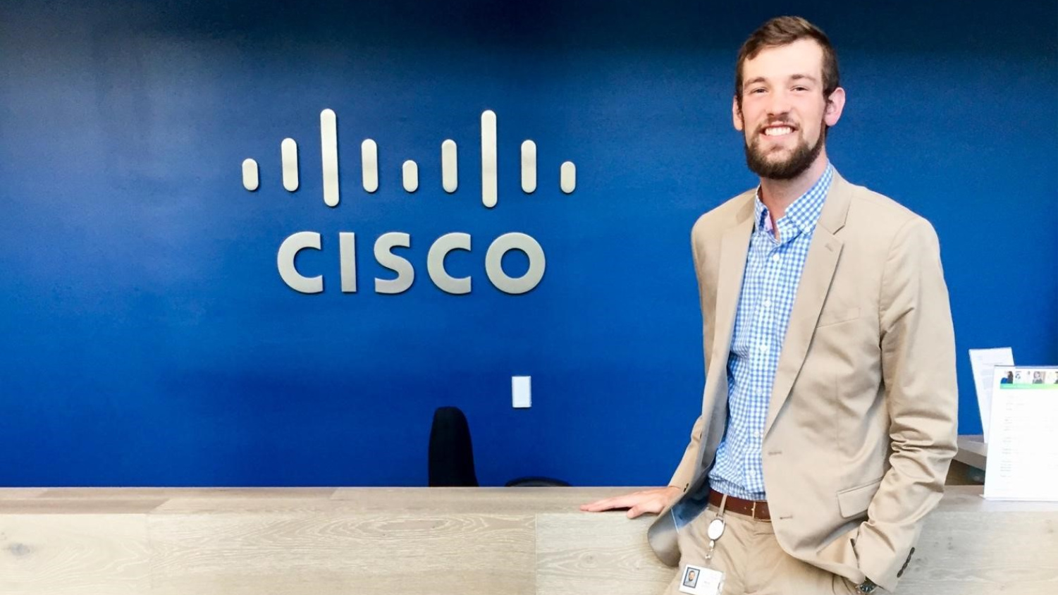 Paul Burke in front of blue wall with Cisco logo