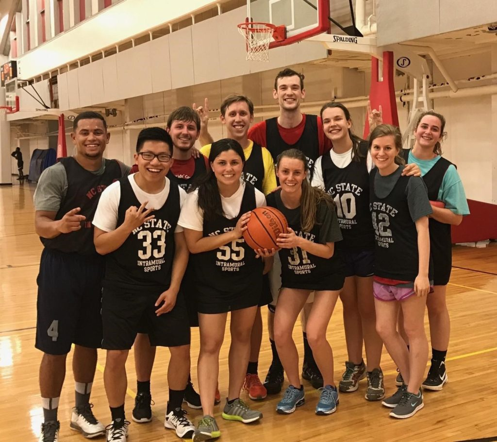 Paul Burke and his intramural basketball team pose on court with basketball